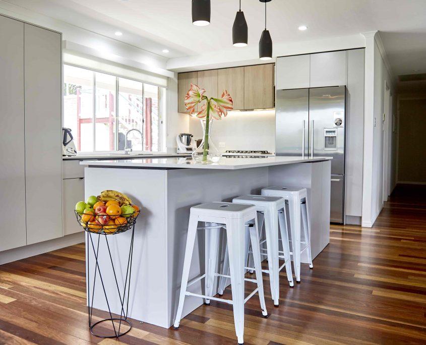 Black pendant lights over kitchen island with white metal stools sunshine coast home