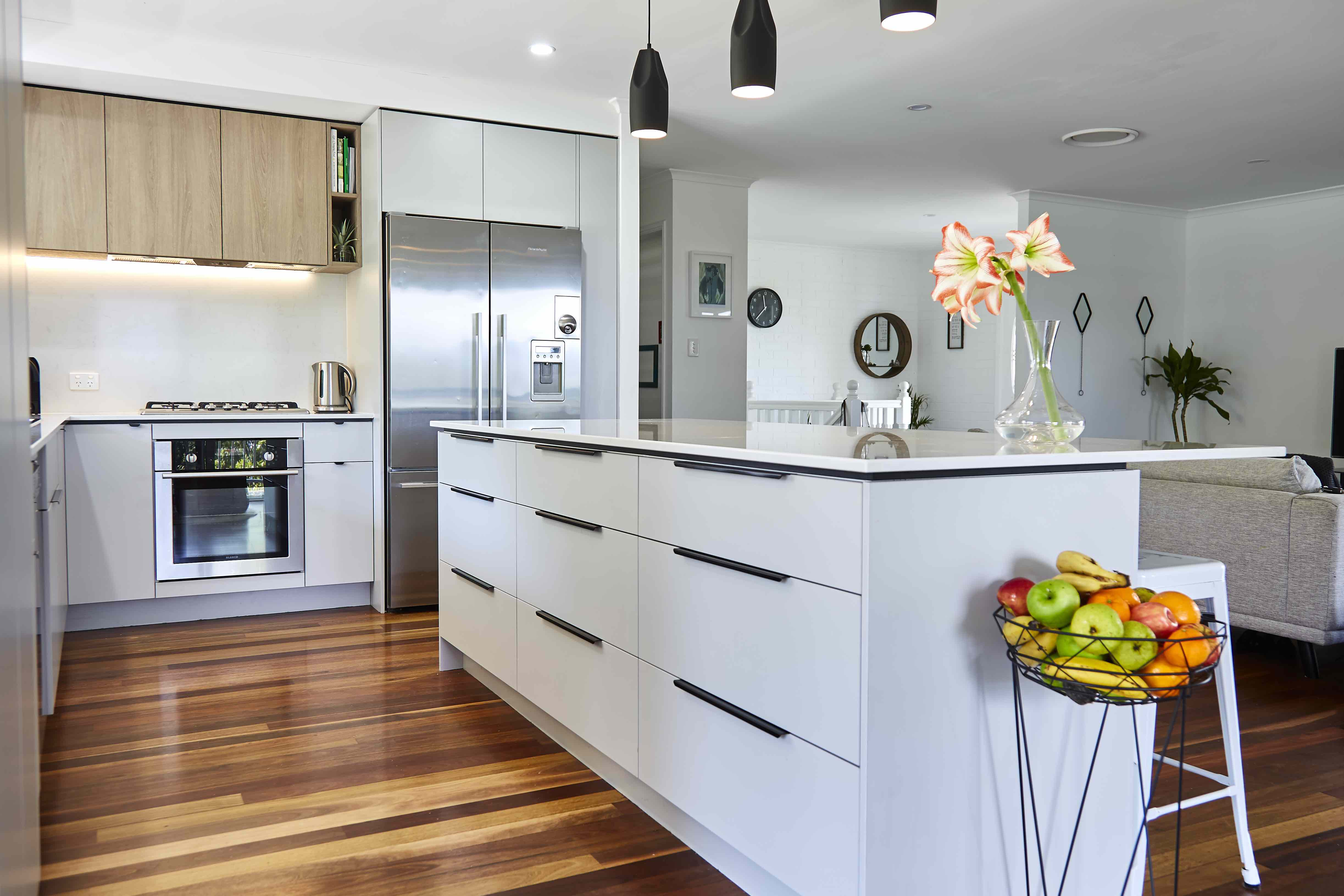 Modern grey kitchen island with black handles and timber flooring