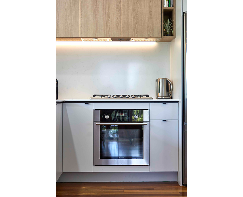Timber wall unit with integrated extractor fan over hob and stainless oven with grey kitchen
