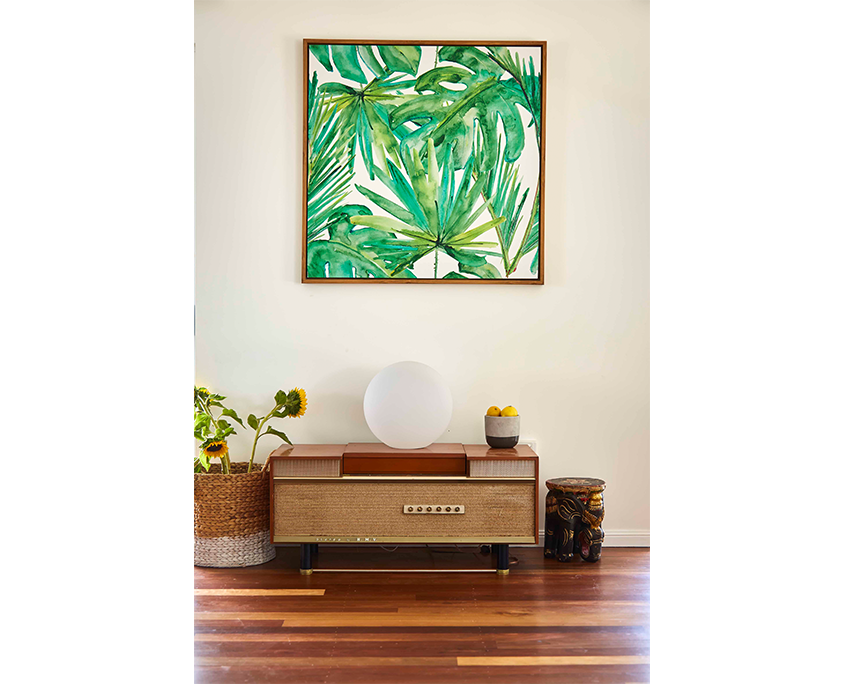 Retro record player and palm fond art beside sunflowers